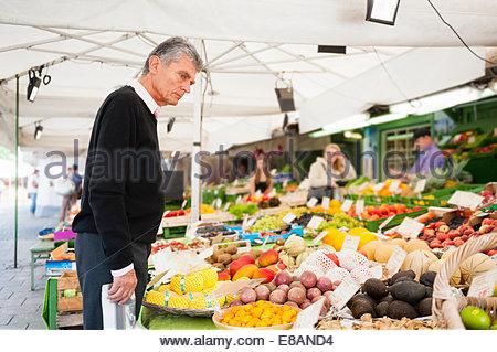 Senior man browsing fruit and vegetables on market stall - Stock Photo