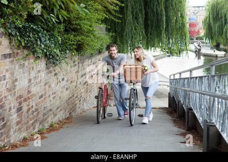 Cyclist couple pushing bike along canal, London, UK - Stock Photo