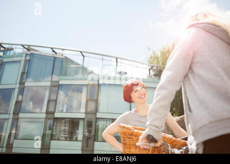Friends chatting, glass-fronted building in background - Stock Photo