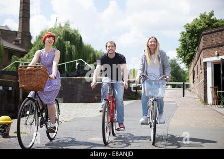 Friends riding bike along canal, East London, UK - Stock Photo