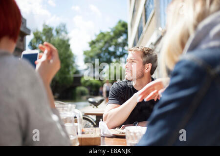 Friends having lunch by canal - Stock Photo