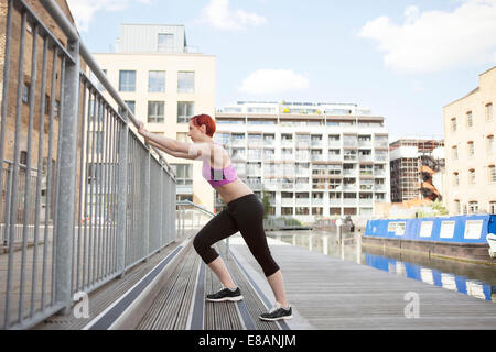 Woman doing stretching exercise, building in background, East London, UK - Stock Photo