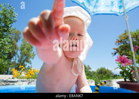 Baby girl in swimming pool pointing finger - Stock Photo