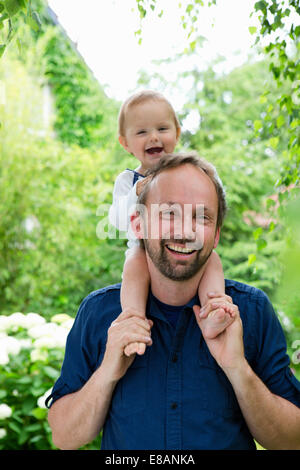Portrait of baby girl sitting on fathers shoulders in garden - Stock Photo