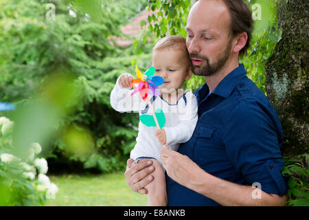 Father and baby daughter playing with pinwheel in garden - Stock Photo