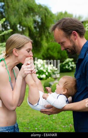 Mother kissing baby daughters feet in garden - Stock Photo
