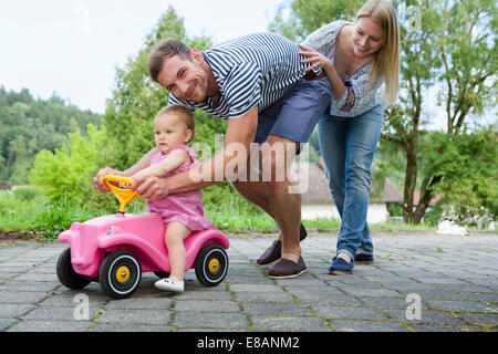 Mid adult couple pushing baby daughter on toy car in garden - Stock Photo