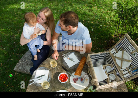 Overhead view of mid adult couple and baby daughter sitting at picnic table in garden - Stock Photo