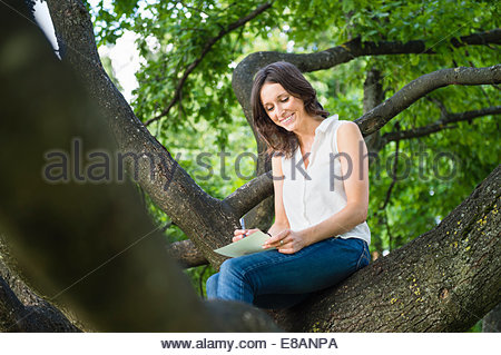 Mid adult woman sitting in woodland tree writing - Stock Photo