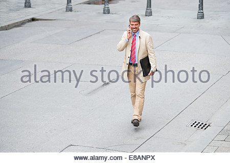 High angle view of mature businessman walking in city chatting on smartphone - Stock Photo