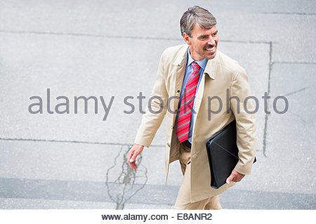 High angle view of mature businessman walking in city carrying portfolio - Stock Photo