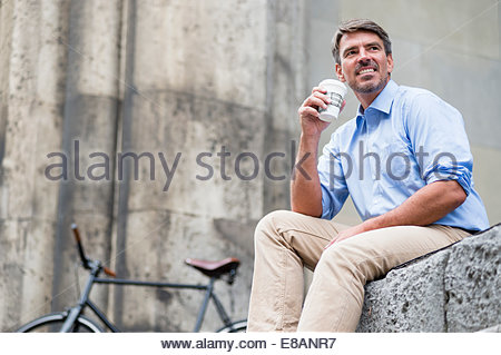 Mature businessman in city drinking takeaway coffee - Stock Photo
