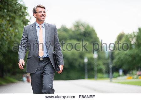 Mature businessman walking along road - Stock Photo