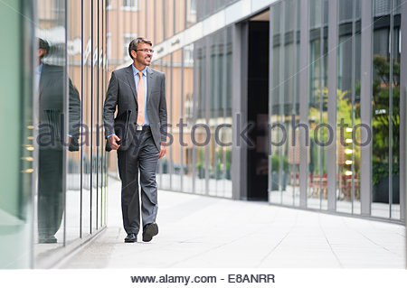 Mature businessman walking outside office building - Stock Photo