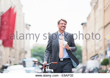 Mature businessman pushing bicycle in street and drinking takeaway coffee - Stock Photo