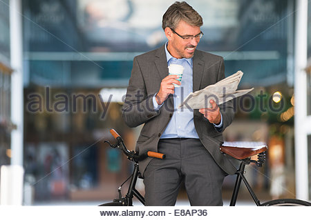 Mature businessman reading newspaper and drinking takeaway coffee - Stock Photo