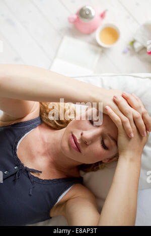 Woman lying on sofa with hands on head - Stock Photo