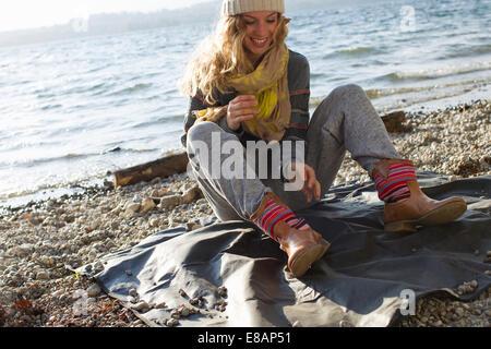 Woman sitting on windy beach - Stock Photo