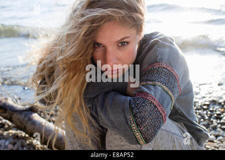 Woman sitting on windy beach