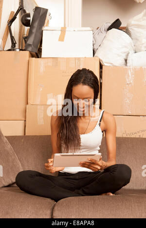 Woman sitting in flat surrounded by boxes - Stock Photo