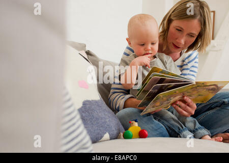 Mature mother and baby daughter on sitting room sofa reading storybook - Stock Photo