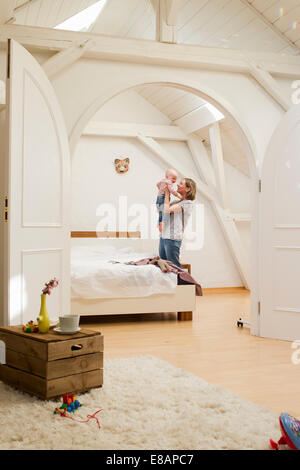 Mature mother holding up baby daughter in bedroom - Stock Photo