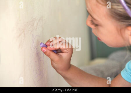 Young girl drawing on wall with chalk - Stock Photo