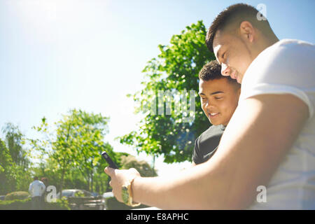 Two young adult friends looking at text message on smartphone - Stock Photo