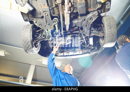 Male college student looking up at car in garage workshop - Stock Photo