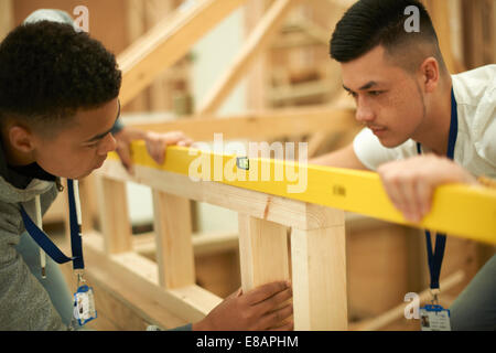 Two male college students using spirit level on frame in woodworking workshop - Stock Photo