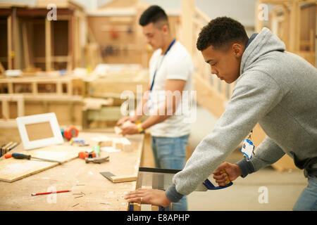 Two male college students in woodworking workshop - Stock Photo
