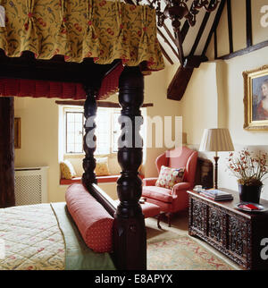 Antique four-poster bed and carved wooden chest in country bedroom with pink armchair - Stock Photo