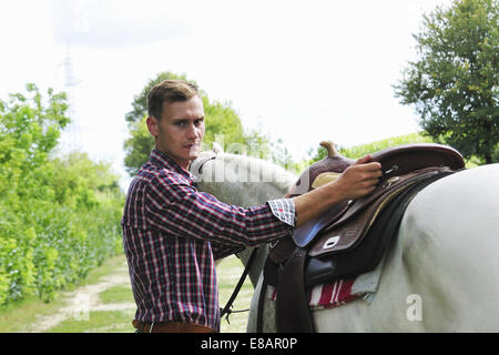 Portrait of young man saddling horse - Stock Photo