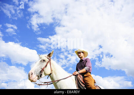Low angle portrait of young man in cowboy gear riding horse - Stock Photo