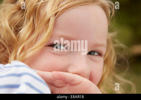 Close up portrait of girl with hand covering mouth - Stock Photo