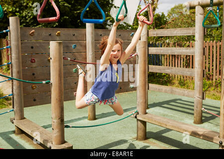 Girl energetically playing on swings in playground