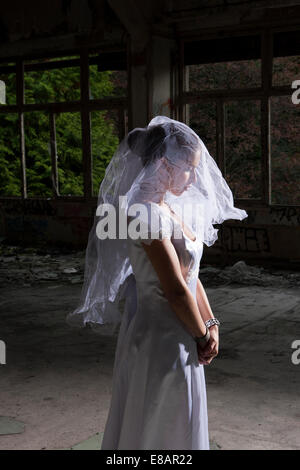 Portrait of bride in empty abandoned interior - Stock Photo