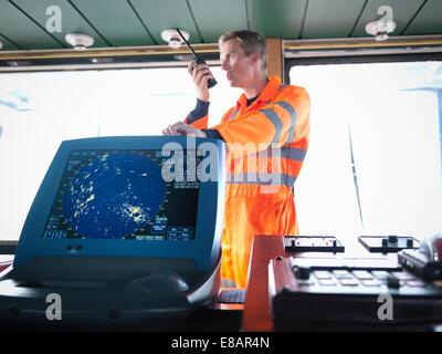 Ship's worker on bridge using walkie-talkie - Stock Photo