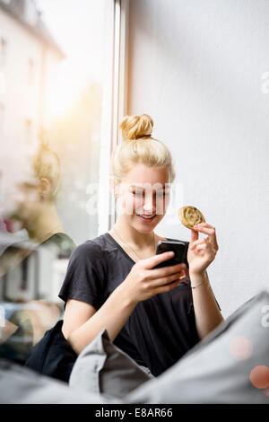 Young woman reading texts on smartphone in window seat - Stock Photo