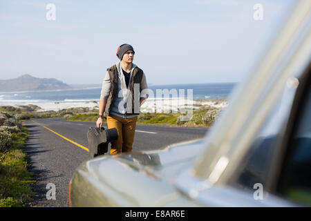 Young man behind parked car with guitar case, Cape Town, Western Cape, South Africa - Stock Photo
