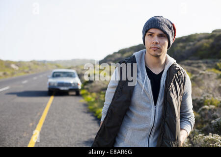 Young man walking along road, Cape Town, Western Cape, South Africa - Stock Photo