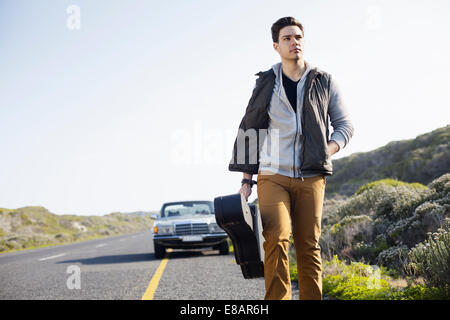 Young man walking along road with guitar case, Cape Town, Western Cape, South Africa - Stock Photo