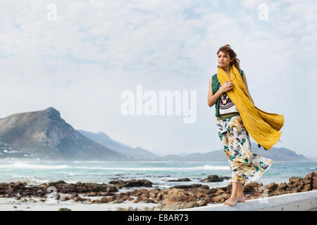 Young woman walking along cement block on beach, Cape Town, Western Cape, South Africa - Stock Photo