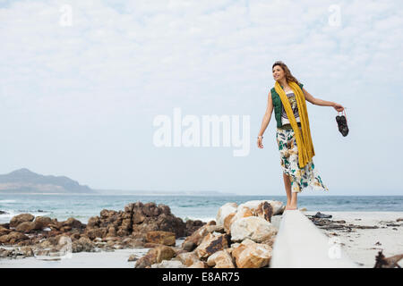 Young woman walking on cement block on beach, Cape Town, Western Cape, South Africa - Stock Photo