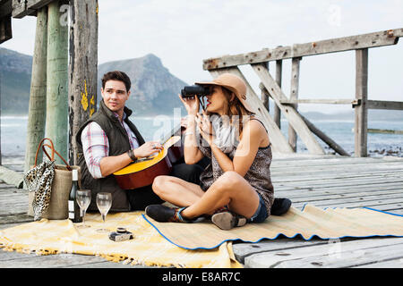 Young couple picnicing on old pier, Cape Town, Western Cape, South Africa - Stock Photo