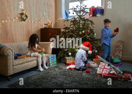 Girl and two brothers opening christmas gifts in sitting room - Stock Photo
