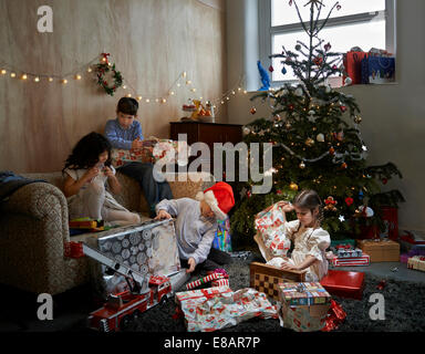 Sisters and brothers opening christmas gifts in sitting room - Stock Photo