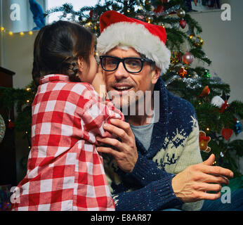 Daughter whispering to father in santa hat at christmas - Stock Photo