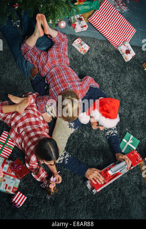Father lying on sitting room floor opening christmas gifts with daughter and son - Stock Photo