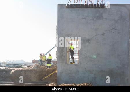 Site manager checking doorway on construction site - Stock Photo